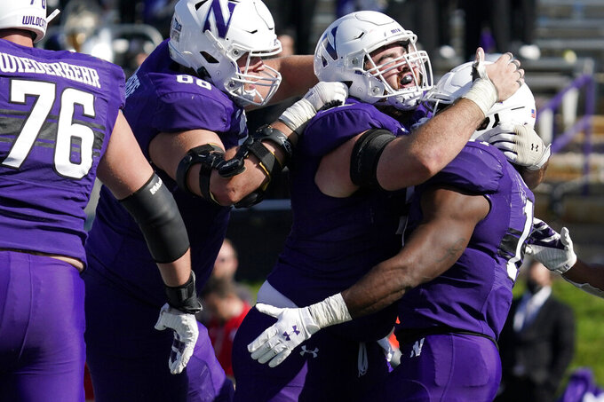 Northwestern running back Andrew Clair, right, celebrates with teammates after scoring a touchdown during the second half of an NCAA college football game against Rutgers in Evanston, Ill., Saturday, Oct. 16, 2021. Northwestern won 21-7. (AP Photo/Nam Y. Huh)