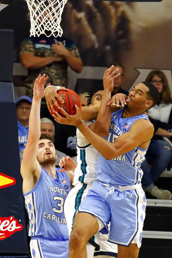 North Carolina's Garrison Brooks (15) takes the ball away from North Carolina Wilmington's Jaylen Sims (30) in front of North Carolina's Andrew Platek (3) during the second half of an NCAA college basketball game in Wilmington, N.C., Friday, Nov. 8, 2019. (AP Photo/Karl B DeBlaker)