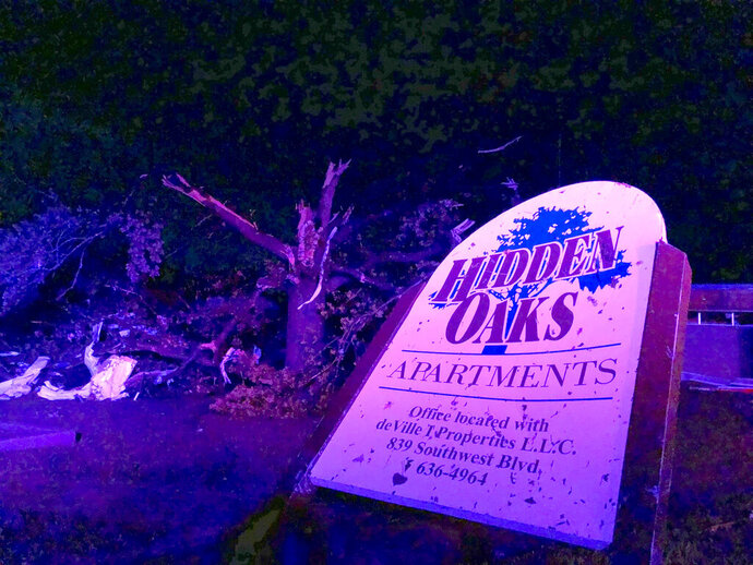 The sign for the Hidden Oaks apartment complex in Jefferson City Missouri stands bent on May 23, 2019, from an apparent tornado in front of a tree that was ripped apart. A