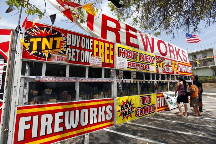 File - In this July 2, 2013, file photo, a family buys fireworks at a TNT Fireworks stand in the City of Monterey Park, Calif. Albuquerque, N.M.; is joining a growing number of communities in California and Texas asking residents to use an app to report illegal fireworks on July 4th instead of calling 911. (AP Photo/Nick Ut, File)
