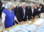 FILE In this file photo taken on Tuesday, April 21, 2020, Belarusian President Alexander Lukashenko talks with an employee during his visit to sewing factory Slavyanka, specializes in producing clothing for adults and children, but recently the production of personal protective equipment has been established to help protect against the coronavirus, in the town of Bobruisk, 150 km (94 miles) southeast of Minsk, Belarus. Last month, Lukashenko abruptly announced that he got the virus himself but had no symptoms and recovered quickly thanks to doing sports. His bravado has angered many in Belarus, and combined with a painful economic fallout from the global pandemic it helped swell the opposition ranks ahead of the vote. (Maxim Guchek/ Pool Photo via AP, File)