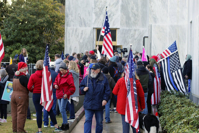 FILE - In this Dec. 21, 2020, file photo, pro-Trump and anti-mask demonstrators hold a rally outside the Oregon State Capitol as legislators meet for an emergency session in Salem, Ore. Prosecutors have leveled criminal charges against a Republican member of the Oregon House of Representatives who let far-right rioters into the state Capitol that day. Rep. Mike Nearman was charged with official misconduct in the first degree and criminal trespass in the second degree. A special committee could recommend he be the first member of the House to be expelled in its 160-year history. (AP Photo/Andrew Selsky, File)