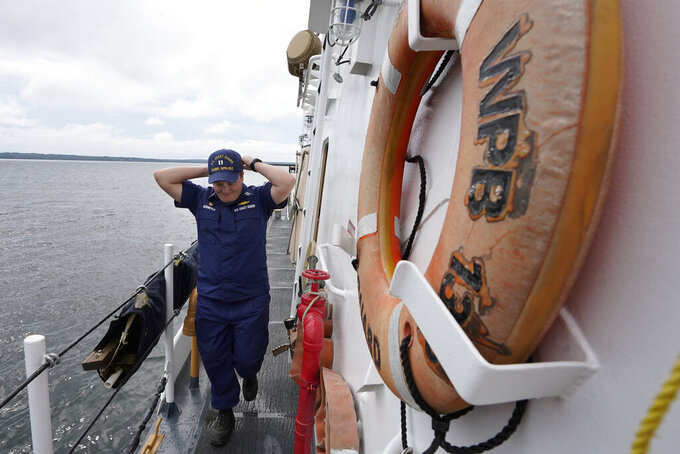 """U.S. Coast Guard Lt. Kelli Normoyle, Commanding Officer of the Coast Guard Cutter Sanibel, adjusts her hat while walking on the deck of the vessel, Thursday, Sept. 16, 2021, at a shipyard in North Kingstown, R.I. Normoyle was one of two cadets who formally started the process to create the CGA Spectrum Diversity Council just a few months after the law known as """"don't ask, don't tell"""" was repealed on Sept. 20, 2011. (AP Photo/Steven Senne)"""