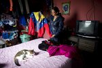 Judith Perez, mother of Karen Palacios, shows the jacket that her daughter wore many times during her performances, in Karen's bedroom in Los Teques in the outskirts of Caracas, Venezuela, Tuesday, July 16, 2019. Karen Palacios who plays the clarinet and was cut from the National Philharmonic for criticizing the government, and who was detained for 6 weeks, was released today. (AP Photo/Ariana Cubillos)