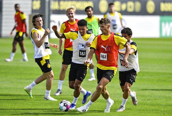 Dortmund's new player Thomas Meunier, right, fights for the ball with Jadon Sancho, left, during the first training session of German Bundesliga club Borussia Dortmund at the training grounds in Dortmund, Germany, Monday, Aug. 3, 2020. (AP Photo/Martin Meissner)