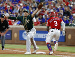 Oakland Athletics first baseman Matt Olson reaches up but is unable to catch the throw to the bag as Texas Rangers' Delino DeShields (3) sprints to first in the fourth inning of the second baseball game of a doubleheader in Arlington, Texas, Saturday, June 8, 2019. DeShields reached on the throwing error by Athletics third baseman Chad Pinder. (AP Photo/Tony Gutierrez)
