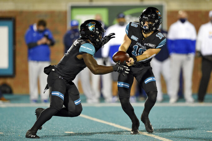 Coastal Carolina quarterback Grayson McCall, right, hands the ball off to CJ Marable during the first half of an NCAA college football game against BYU Saturday, Dec. 5, 2020, in Conway, S.C. (AP Photo/Richard Shiro)