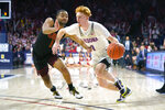 Arizona guard Nico Mannion (1) drives on Southern California guard Kyle Sturdivant during the second half of an NCAA college basketball game Thursday, Feb. 6, 2020, in Tucson, Ariz. Arizona won 85-80 (AP Photo/Rick Scuteri)