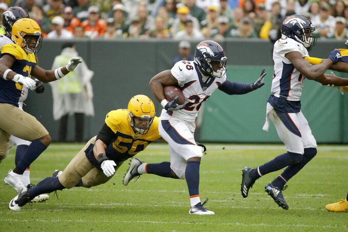 Denver Broncos running back Royce Freeman (28) carries with the ball as Green Bay Packers inside linebacker Blake Martinez (50) defends during the first half of an NFL football game Sunday, Sept. 22, 2019, in Green Bay, Wis. (AP Photo/Mike Roemer)