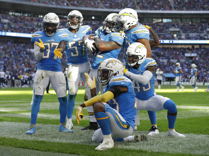 FILE - In this Sunday, Oct. 21, 2018, file photo, Los Angeles Chargers players celebrate after making a turnover during the first half of an NFL football game against the Tennessee Titans at Wembley stadium in London. On Tuesday, April 16, 2019, the Chargers announced they will wear their historic powder-blue jerseys as their primary home uniforms in the upcoming season. (AP Photo/Matt Dunham, File)