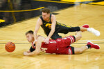 Wisconsin guard Brad Davison (34) fights for a loose ball with Iowa guard Jordan Bohannon during the first half of an NCAA college basketball game, Sunday, March 7, 2021, in Iowa City, Iowa. (AP Photo/Charlie Neibergall)