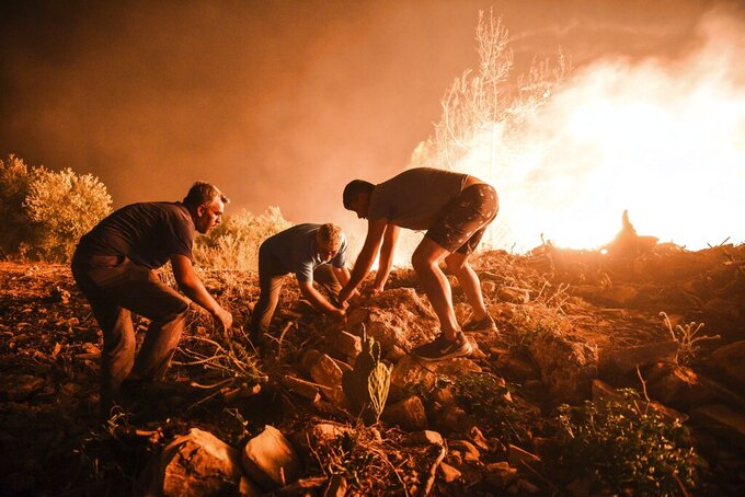 Local villagers try to get the fire under control in Kirli village near the town of Manavgat, in Antalya province, Turkey, early Friday July 30, 2021. The fire that continued all night could not be brought under control and people living in the village started to evacuate. Wildfires are common in Turkey's Mediterranean and Aegean regions during the arid summer months, although some previous forest fires have been blamed on arson. (AP Photo)