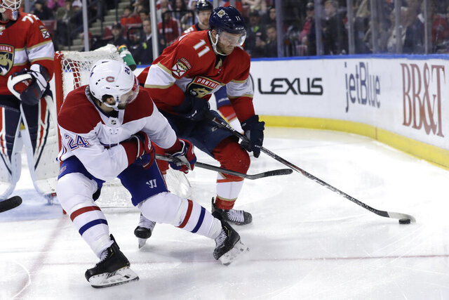 Florida Panthers left wing Jonathan Huberdeau (11) skates with the puck as Montreal Canadiens center Phillip Danault (24) defends during the second period of an NHL hockey game, Sunday, Dec. 29, 2019, in Sunrise, Fla. (AP Photo/Lynne Sladky)