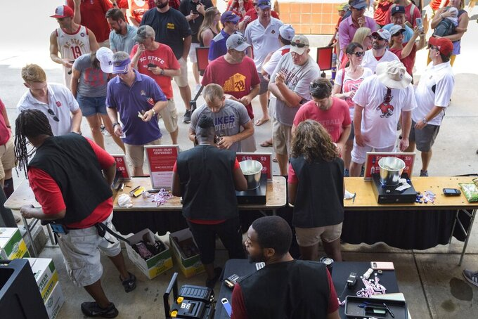 Fans line up at a concession stand that sells beer during an NCAA college football game between North Carolina State and East Carolina at Carter Finley Stadium in Raleigh, N.C., Saturday, Aug 31, 2019.  There's a growing trend at Atlantic Coast Conference football games: alcohol sales to the general public.  Now everyone can enjoy their beverage of choice at most ACC stadiums, not just boosters and donors. (Bryan Cereijo/The News & Observer via AP)