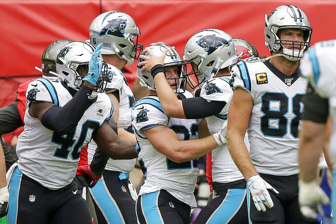 Carolina Panthers running back Christian McCaffrey (22) is congratulated by quarterback Kyle Allen after scoring a touchdown against the Tampa Bay Buccaneers during the first quarter of an NFL football game, Sunday, Oct. 13, 2019, at Tottenham Hotspur Stadium in London. (AP Photo/Tim Ireland)