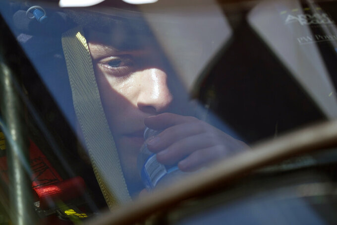 Santino Ferrucci take a drink of water as he sits in his car during a practice session for the Indianapolis 500 auto race at Indianapolis Motor Speedway, Friday, Aug. 14, 2020, in Indianapolis. (AP Photo/Darron Cummings)