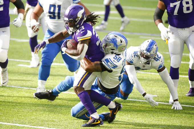 Minnesota Vikings running back Dalvin Cook (33) is tackled by Detroit Lions linebacker Jamie Collins Sr. (58) during the first half of an NFL football game, Sunday, Nov. 8, 2020, in Minneapolis. (AP Photo/Bruce Kluckhohn)