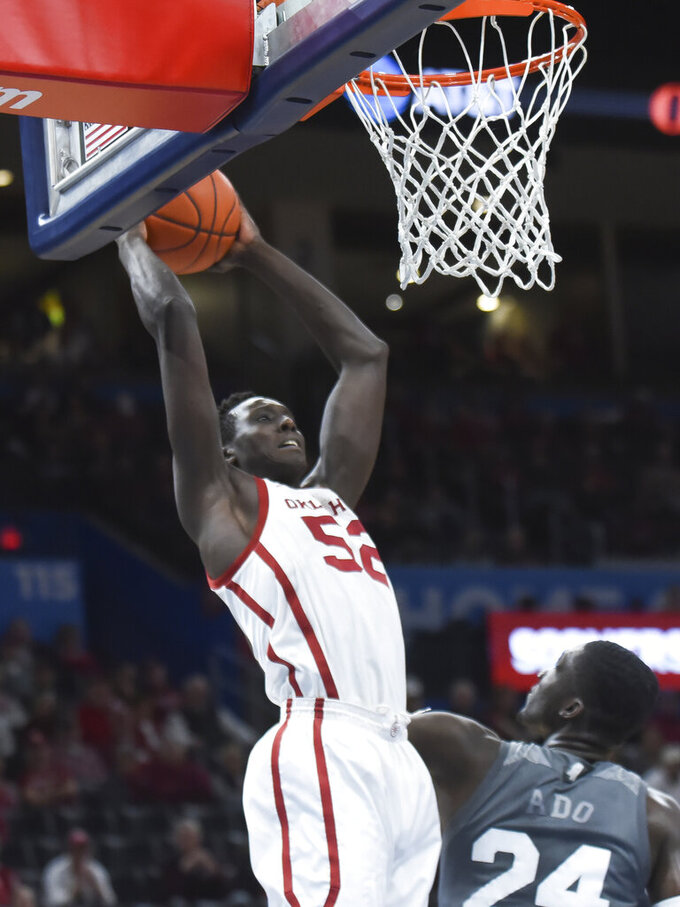 Oklahoma forward Kur Kuath (52) goes up for a shot over Mississippi State forward Abdul Ado (24) during the first half of an NCAA college basketball game in Oklahoma City, Saturday, Jan. 25, 2020. (AP Photo/Kyle Phillips)