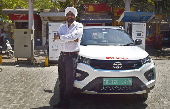 An attendant of a public charging station for electric vehicles sits idle in New Delhi, India, Thursday, April 1, 2021. India has ambitions to expand use of electric vehicles to wean itself from polluting fossil fuels, but EVs are still a rarity on its congested highways. A lack of charging stations and poor quality batteries are discouraging drivers from switching over. (AP Photo/Neha Mehrotra)