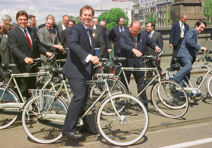 FILE - In this Tuesday, June 17, 1997 ,file photo, Britain's Prime Minister Tony Blair, foreground, mounts a bike, along with European leaders in Amsterdam. One of Blair's ambitions after his Labour Party won a landslide election victory in May, 1997, was to put Britain at the