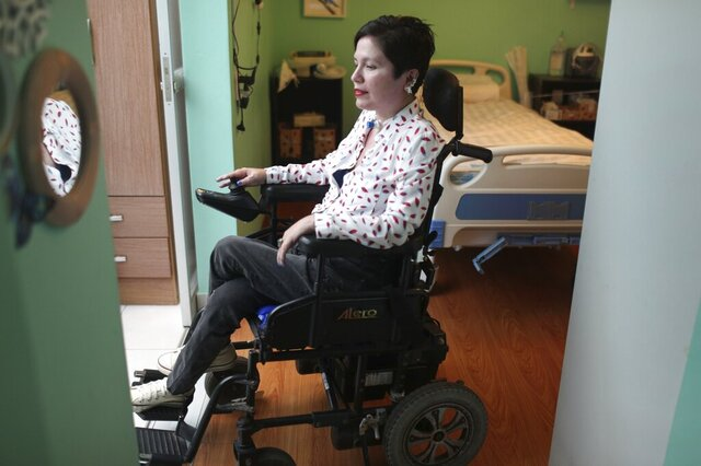 "In this Dec. 18, 2019 photo, Ana Estrada, a 42-year-old Peruvian psychologist who is almost completely paralyzed by a terminal illness and yearns to be legally allowed to end her own life, rides her motorized wheelchair through her home in Lima, Peru. ""In Peru, 'mercy killing' is a crime carrying three years in jail, so any person or doctor who wants to help her would be committing a crime,"" Public Defender Walter Gutiérrez said. (AP Photo/Martin Mejia)"