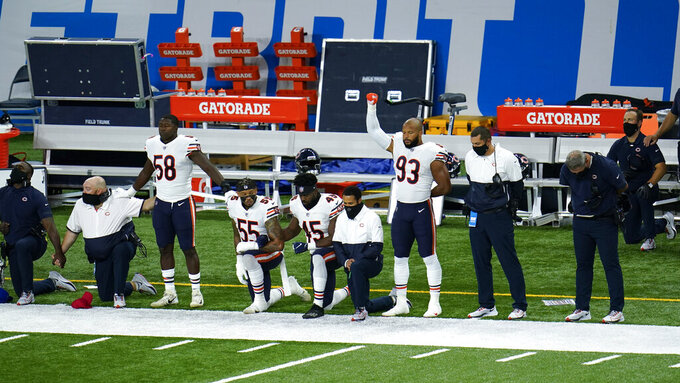 Chicago Bears Roquan Smith (58), Josh Woods (55), Joel Iyiegbuniwe (45) and James Vaughters (93) listen during the national anthem before an NFL football game against the Detroit Lions in Detroit, Sunday, Sept. 13, 2020. (AP Photo/Paul Sancya)
