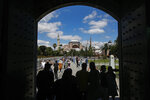 Visitors walk towards the Byzantine-era Hagia Sophia, in the historic Sultanahmet district of Istanbul, Saturday, July 11, 2020. Turkish President Recep Tayyip Erdogan is scheduled to join hundreds of worshipers Friday, July 24, for the first Muslim prayers at the Hagia Sophia in 86 years, weeks after a controversial high court ruling paved the way for the landmark monument to be turned back into a mosque. (AP Photo/Emrah Gurel)