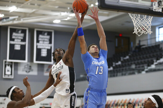 Providence's Jimmy Nichols, Jr. (5) ad Creighton's Christian Bishop (13) battle for a rebound during the second half of an NCAA college basketball game Saturday, Jan. 2, 2021, in Providence, R.I. (AP Photo/Stew Milne)