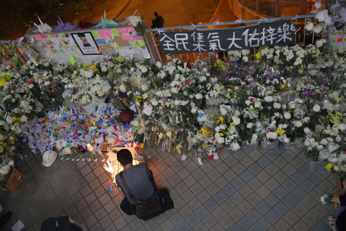 A protester light candles near flowers and a banner which reads