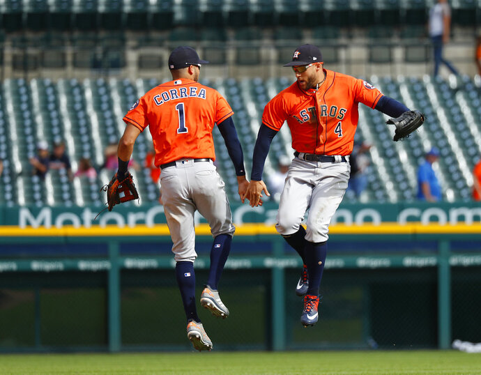 Houston Astros' Carlos Correa (1) and George Springer (4) celebrate their 5-4 win after a baseball game against the Detroit Tigers in Detroit, Wednesday, Sept. 12, 2018. (AP Photo/Paul Sancya)