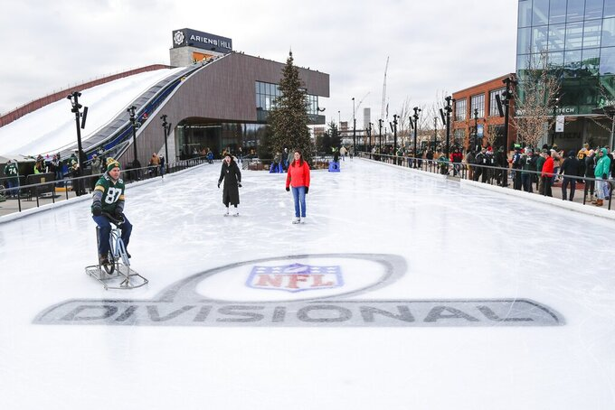 Fans ice skate near Lambeau Field before an NFL divisional playoff football game between the Green Bay Packers and the Seattle Seahawks Sunday, Jan. 12, 2020, in Green Bay, Wis. (AP Photo/Matt Ludtke)