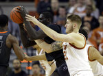 Texas forward Dylan Osetkowski (21) pressures Oklahoma State forward Yor Anei, left, during the second half of an NCAA college basketball game, Saturday, Feb. 16, 2019, in Austin, Texas. Texas won 69-57. (AP Photo/Eric Gay)