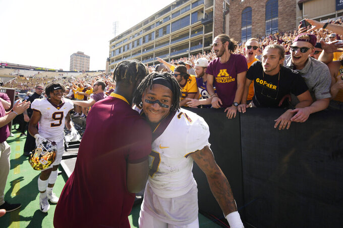 Minnesota wide receiver Chris Autman-Bell, front right, is congratulated by a cheerleader after an NCAA college football game against Colorado, Saturday, Sept. 18, 2021, in Boulder, Colo. Minnesota won 30-0. (AP Photo/David Zalubowski)