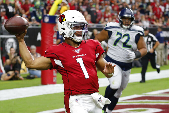 Arizona Cardinals quarterback Kyler Murray (1) throws as Seattle Seahawks defensive tackle Al Woods (72) pursues during the first half of an NFL football game, Sunday, Sept. 29, 2019, in Glendale, Ariz. (AP Photo/Ross D. Franklin)