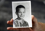 In this Wednesday, Aug. 21, 2019 photo, Greg Hunt holds a school photo of himself in St. Petersburg, Fla. Attorneys for victims from around the country of alleged childhood sex abuse by Boy Scout officials say they are preparing to sue the organization in New Jersey when the state's new civil statute of limitations goes into effect. Hunt, 62, is planning to be on the suit in New Jersey. (AP Photo/Chris O'Meara)
