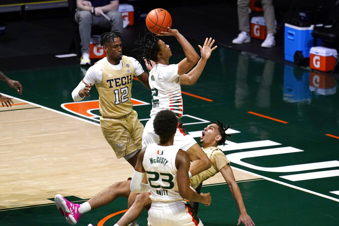 Miami guard Isaiah Wong (2) commits an offensive foul as Georgia Tech guard Michael Devoe, right, falls to the court during the first half of an NCAA college basketball game, Saturday, Feb. 20, 2021, in Coral Gables, Fla. (AP Photo/Lynne Sladky)