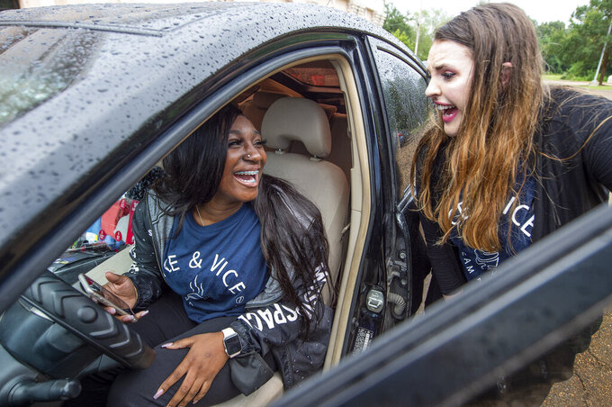 Sirayah Miller, left, smiles while sitting behind the wheel of her new car,   as she talks with Sarah Dale Harmon, right, co-owner of Ice & Vice frozen treat shop in Madison, Miss., Friday, Aug. 20, 2021. Miller, who has aged-out of foster care, is the first recipient of a transportation scholarship offered to employees of Ice & Vice. (Barbara Gauntt/The Clarion-Ledger via AP)