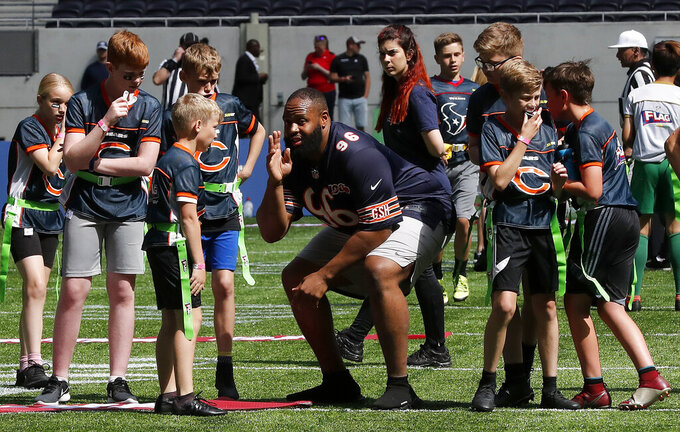 NFL Player Akiem Hicks of the Chicago Bears coaches a young team during the final tournament for the UK's NFL Flag Championship, featuring qualifying teams from around the country, at the Tottenham Hotspur Stadium in London, Wednesday, July 3, 2019. The new stadium will host its first two NFL London Games later this year when the Chicago Bears face the Oakland Raiders and the Carolina Panthers take on the Tampa Bay Buccaneers. (AP Photo/Frank Augstein)