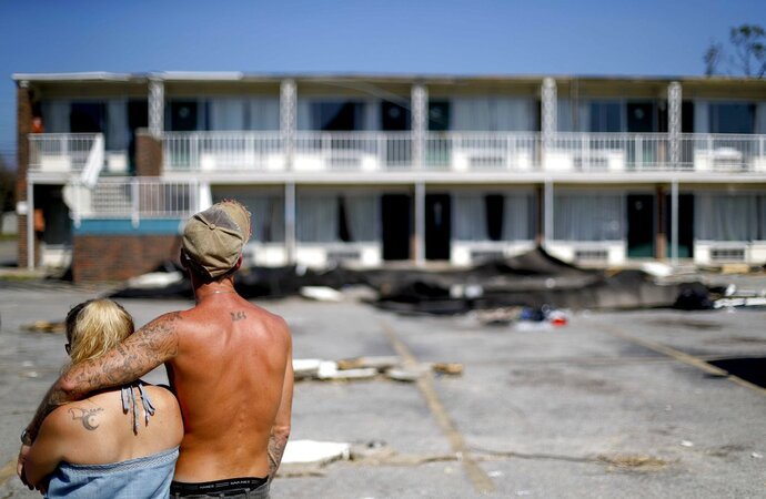 Residents line up for food from the Red Cross outside a damaged motel, Tuesday, Oct. 16, 2018, in Panama City, Fla., where many residents continue to live in the aftermath of Hurricane Michael. Some residents rode out the storm and have no place to go even though many of the rooms at the motel are uninhabitable. (AP Photo/David Goldman)