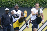 Pittsburgh Steelers head coach Mike Tomlin, left, watches as offensive tackle Jarron Jones (74), center, and tight end Zach Gentry (81) laugh as they warm up during an NFL football practice, Thursday, July 22, 2021, in Pittsburgh. (AP Photo/Keith Srakocic)