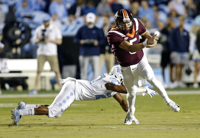 Virginia Tech quarterback Ryan Willis (5) breaks a tackle-attempt by North Carolina's Chris Collins (17) during the first half of an NCAA college football game in Chapel Hill, N.C., Saturday, Oct. 13, 2018. Willis scored on the play. (AP Photo/Gerry Broome)