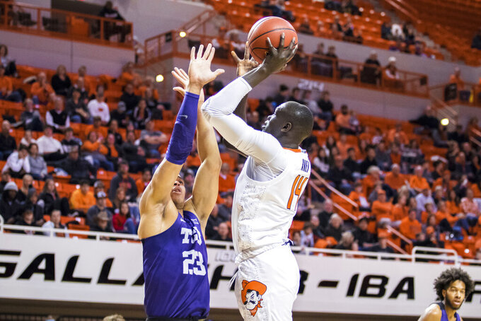 Oklahoma State center Yor Anei shoots over TCU's Jaedon Ledee during an NCAA college basketball game Wednesday, Feb. 5, 2020, in Stillwater, Okla. (Devin Lawrence/Tulsa World via AP)