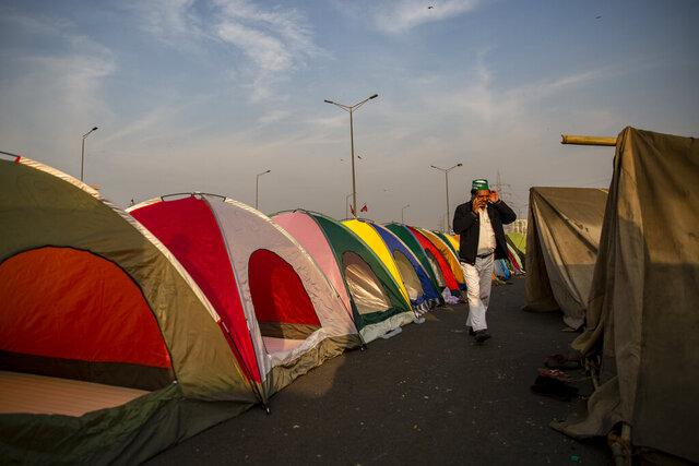 A farmer speaks on his mobile as he walks past tents put up in the middle of a major highway which is blocked in a protest against new farm laws at the Delhi-Uttar Pradesh state border, India, Wednesday, Jan. 20, 2021. Farmers have been blockading highways connecting New Delhi to northern India for nearly seven weeks against new farm laws, obstructing transportation and dealing a blow to manufacturing and businesses in the north. Farmers fear the government will stop buying grain at minimum guaranteed prices and that corporations will then push prices down under the new laws. (AP Photo/Altaf Qadri)