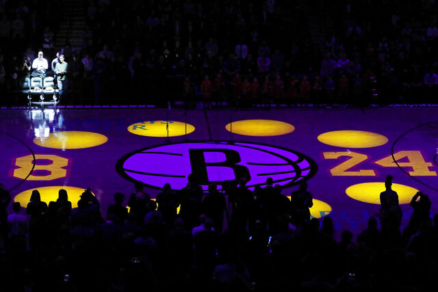 Flowers are placed on empty chairs that retired Los Angeles Lakers superstar Kobe Bryant and his daughter Gianna occupied Dec. 21, 2019, when they attended a Brooklyn Nets game at the Barclays Center during a pregame tribute to Byant before an NBA basketball game between the Nets and the Detroit Pistons, Wednesday, Jan. 29, 2020, in New York. (AP Photo/Kathy Willens)