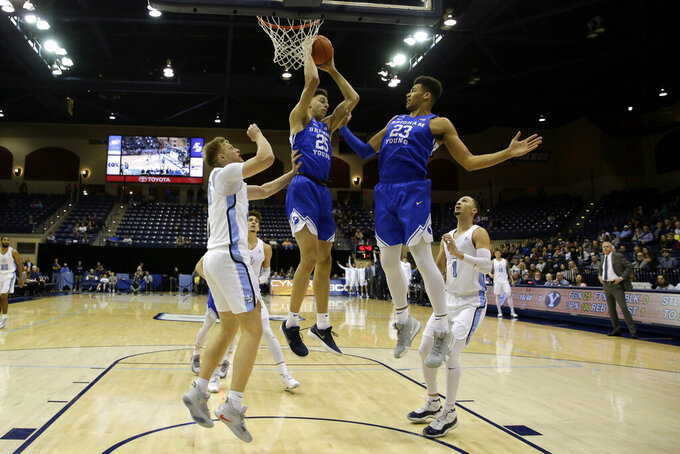 Brigham Young forward Gavin Baxter, center, grabs a rebound alongside teammate forward Yoeli Childs, right, as San Diego forward Yauhen Massalski defends, left, during the first half of an NCAA college basketball game Thursday, Feb. 14, 2019, in San Diego. (AP Photo/Gregory Bull)
