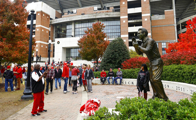 Fans take photos with a statue of Alabama head coach Nick Saban outside the stadium before an NCAA college football game against Auburn, Saturday, Nov. 24, 2018, in Tuscaloosa, Ala. (AP Photo/Butch Dill)