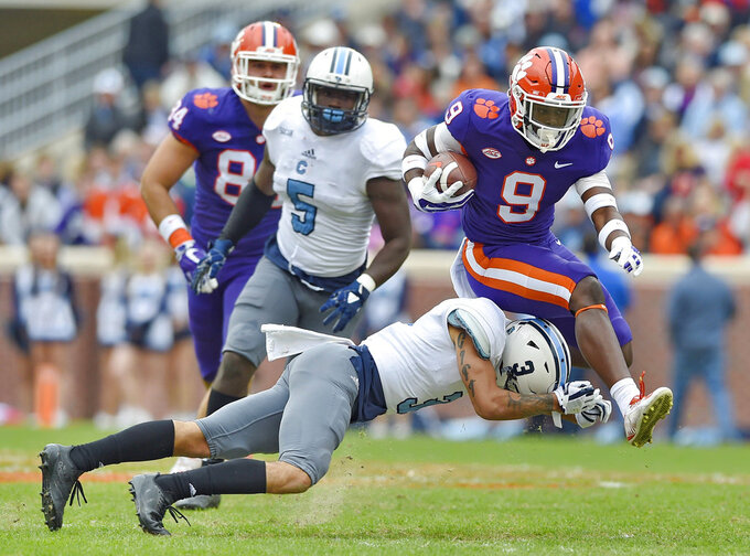 Clemson's Travis Etienne (9) bounds over Citadel's Wally Wilmore to gain a first down during the first half of an NCAA college football game Saturday, Nov. 18, 2017, in Clemson, S.C. (AP Photo/Richard Shiro)