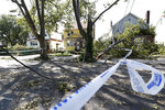 Police tape cordons off a street in Queens where trees fell atop a house, downing power lines and blocking the front entrance of a adjacent home in the wake of Tropical Storm Isaias, Wednesday, Aug. 5, 2020, in New York. The storm passed through New York Tuesday afternoon as it made it's way up the East coast of the United States. (AP Photo/Kathy Willens)