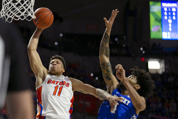 Florida forward Keyontae Johnson (11) goes for the dunk against Kentucky forward Nick Richards (4) during the first half of an NCAA college basketball game Saturday, March 7, 2020, in Gainesville, Fla. (AP Photo/Alan Youngblood)