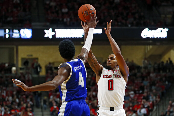 Texas Tech's Kyler Edwards (0) tries to shoot the ball over Eastern Illinois' Marvin Johnson (4) during the first half of an NCAA college basketball game Tuesday, Nov. 5, 2019, in Lubbock, Texas. (AP Photo/Brad Tollefson)